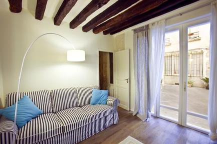 This charming, modern apartment of 27 square meters, characterized by on-site beams in the ceiling and stone walls, is situated on the ground floor of a typical nineteenth-century Parisian building, w